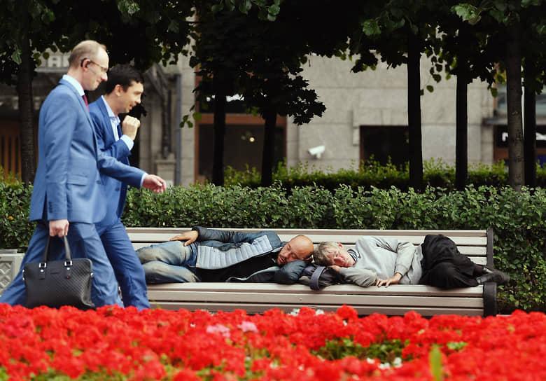 7 сентября. Москва. Мужчины в деловых костюмах проходят мимо спящих на скамейке людей