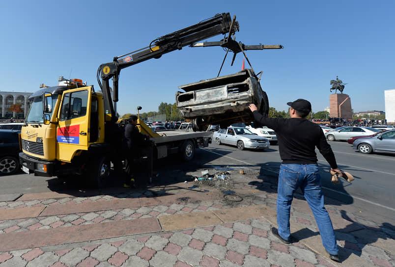 Эвакуатор забирает сожженную машину в центре Бишкека