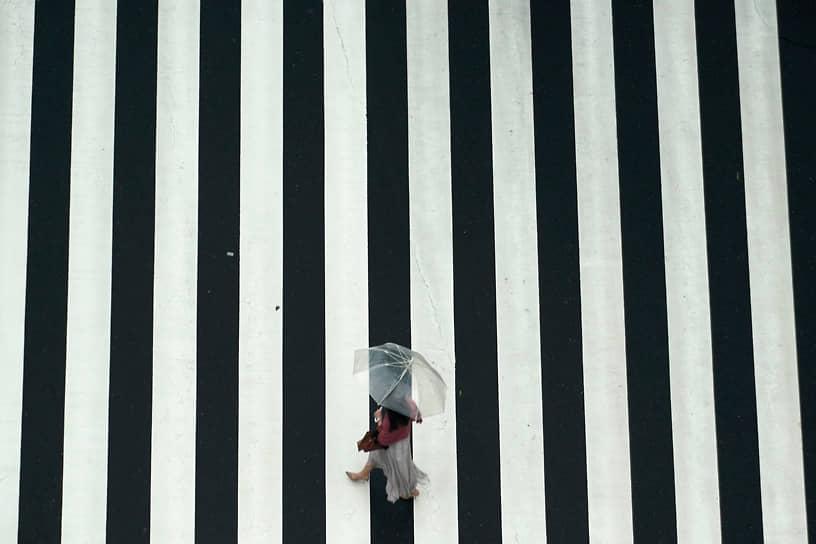Токио, Япония. Женщина идет по пешеходному переходу