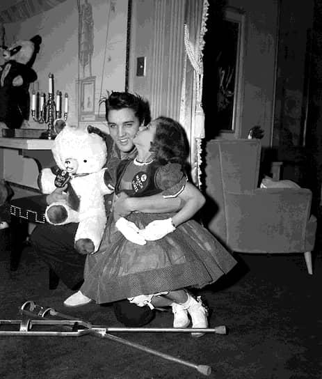 Певец Элвис Пресли с Мэри Кослоски, девочкой с плаката «Марш даймов», и плюшевым медведем, предназначенным для продажи с благотворительного аукциона