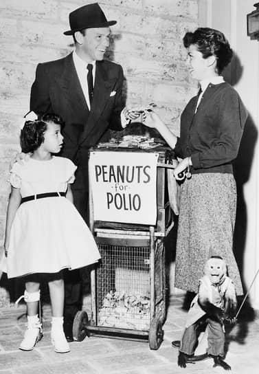 Певец Фрэнк Синатра покупает пакетик арахиса у своей 15-летней дочери Нэнси и пятилетней жертвы полиомиелита Филлис Таунсенд. В январе 1955 года более миллиона американских подростков продавали на улицах арахис для сбора средств на борьбу с полиомиелитом