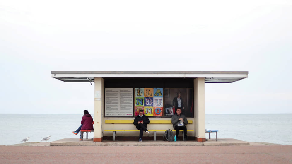 Лландидно, Великобритания. Люди ждут на автобусной остановке в Уэльсе
