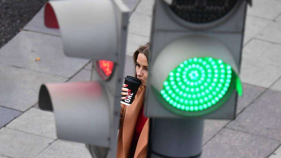 Москва, Россия. Девушка со стаканом кофе у светофора