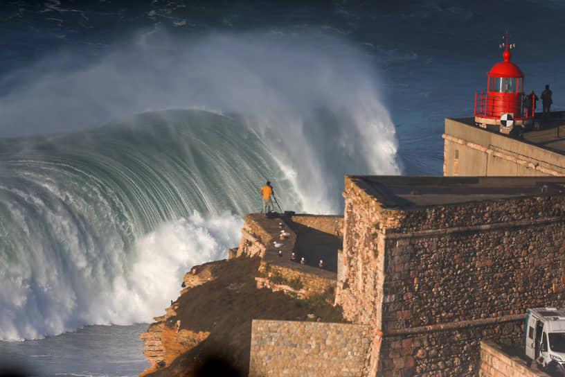 Назаре, Португалия. Люди собираются, чтобы посмотреть на серферов