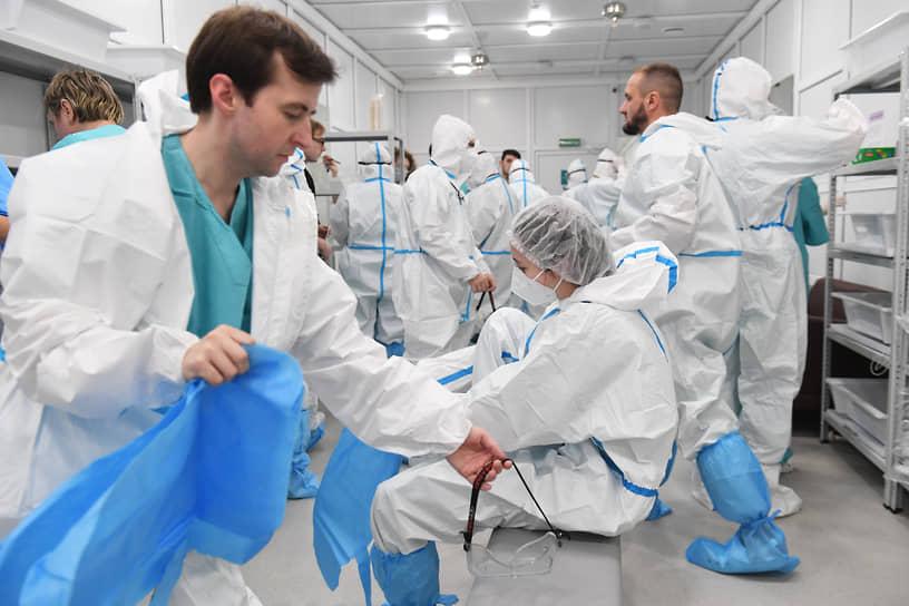 В первую очередь во временный госпиталь поступают с легкой и средней тяжестью течения болезни <br>На фото: медики в защитных костюмах