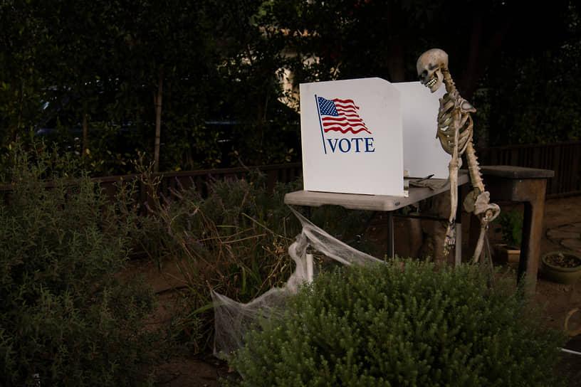 Калифорния, США. Скелет рядом с имитацией кабинки для голосования на выборах президента
