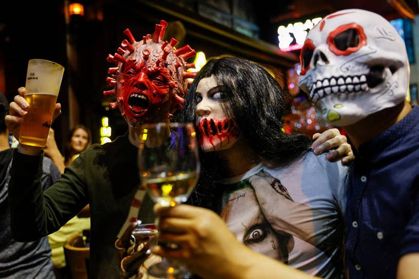 Гонконг, Китай. Празднование Хэллоуина в ночном клубе. Один из мужчин надел маску с изображением коронавируса