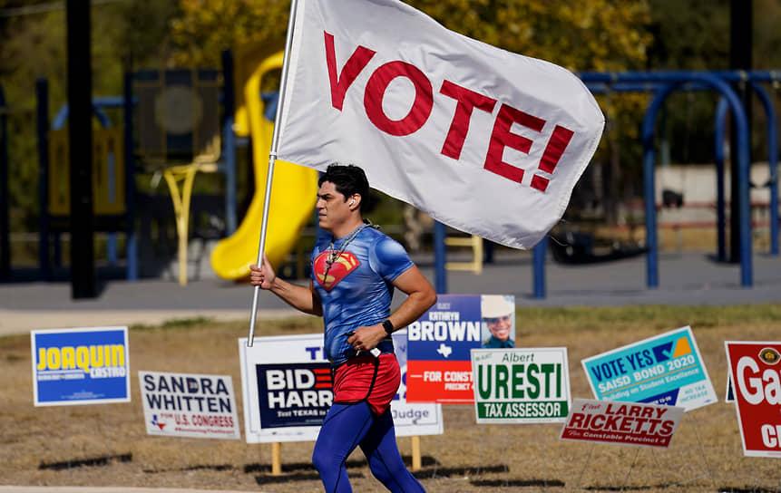 Сан-Антонио, Техас. Мужчина в костюме Супермена с флагом, призывающим проголосовать