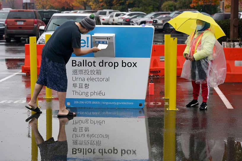 Рентон, Вашингтон. Избиратель опускает свой бюллетень в урну для голосования