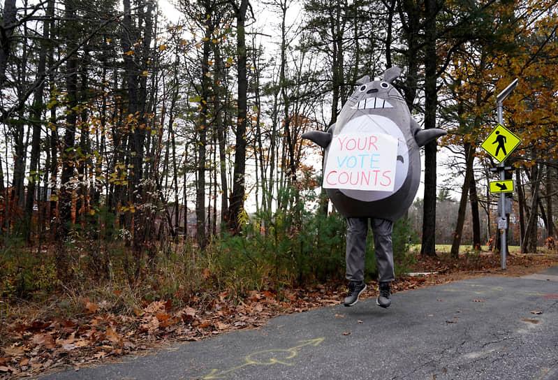 Брансуик, Мэн. Мужчина в костюме персонажа мультфильма «Мой сосед Тоторо» держит табличку с надписью «Ваш голос имеет значение» около избирательного участка