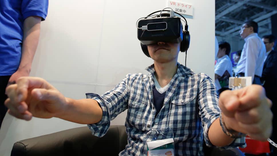 Посетитель международной выставки передовых технологий в Токио тестирует VR-симуляцию поездки по оживленным улицам города
