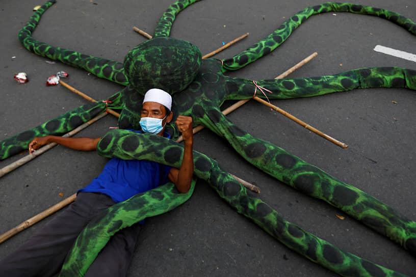 Джакарта, Индонезия. Демонстрант на искусственном осьминоге во время акции против реформ трудового законодательства