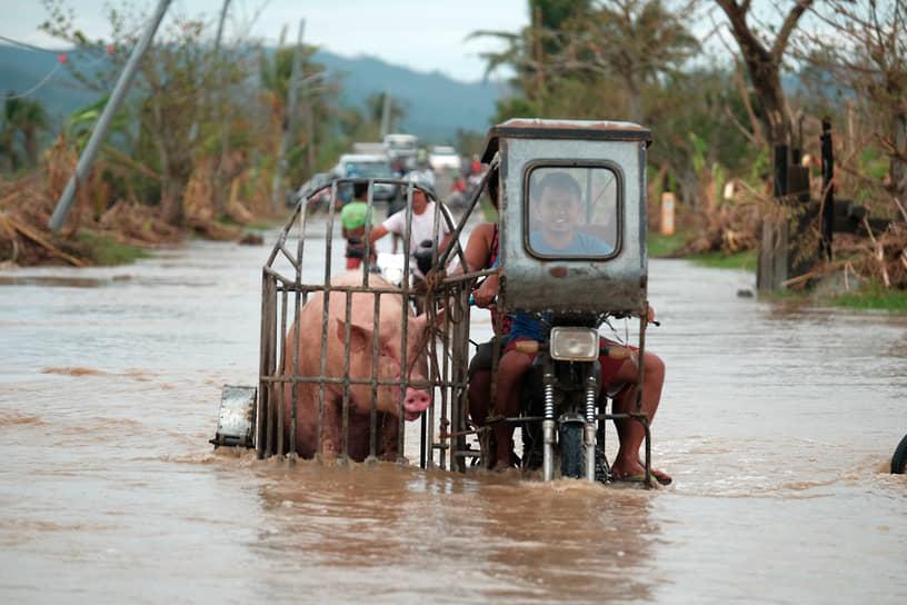 Албай, Филиппины. Местные жители едут по дороге, затопленной из-за тайфуна «Вамко»