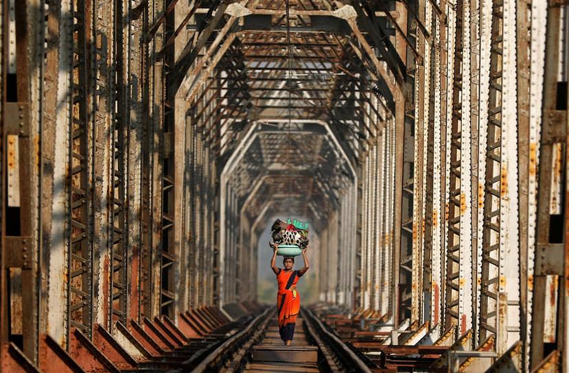 Мумбаи, Индия. Женщина с багажом идет по железнодорожному пути