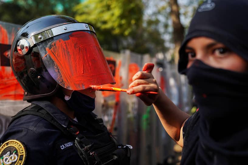 Мехико, Мексика. Участница феминистского движения на акции протеста красит шлем сотрудника правоохранительных органов