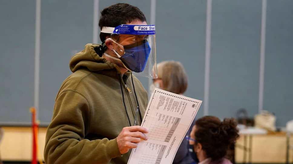 Избиратель в двух масках и защитном экране голосует на избирательном участке в Портленде