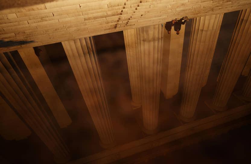 Вашингтон, США. Люди отражаются в луже у мемориала Линкольна