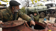 Местный житель наливает воду в бочку из автоцистерны миротворческих сил