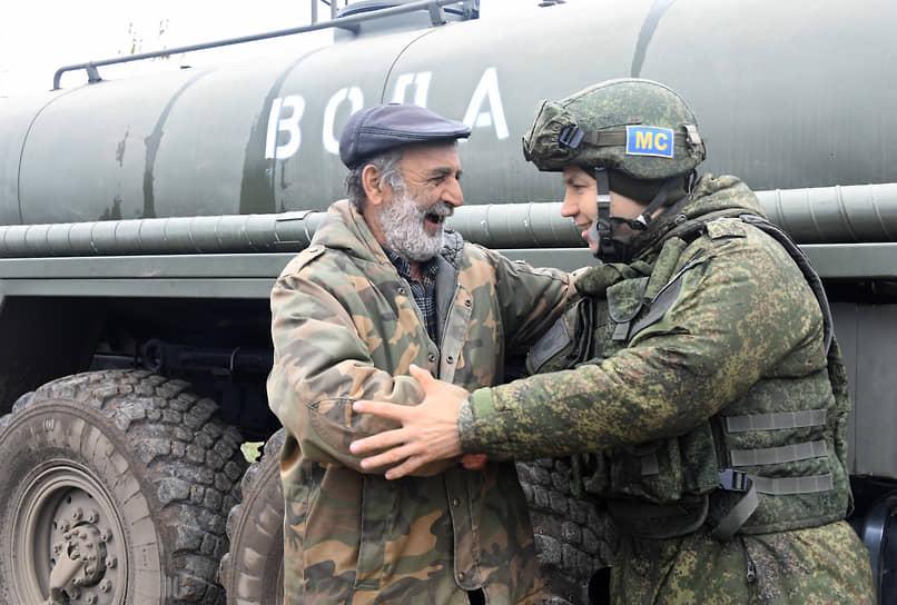 Местный житель разговаривает с военнослужащим миротворческих сил у автоцистерны с водой