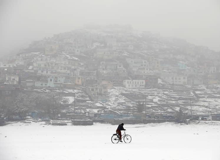 Кабул, Афганистан. Местный житель едет на велосипеде во время снегопада