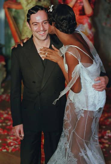 В 1995 году по приглашению главы конгломерата LVMH Джон Гальяно возглавил модный дом Givenchy. В октябре 1996 года его назначили креативным директором дома Christian Dior, которым до этого руководил Джанфранко Ферре<br>На фото: Джон Гальяно с моделью Наоми Кэмпбелл во время показа коллекции прет-а-порте в 1998 году