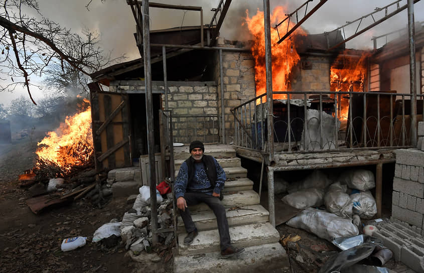 Карегах, Нагорный Карабах. Местный житель возле горящего дома в Лачинском районе, который должен отойти Азербайджану по условиям мирного соглашения