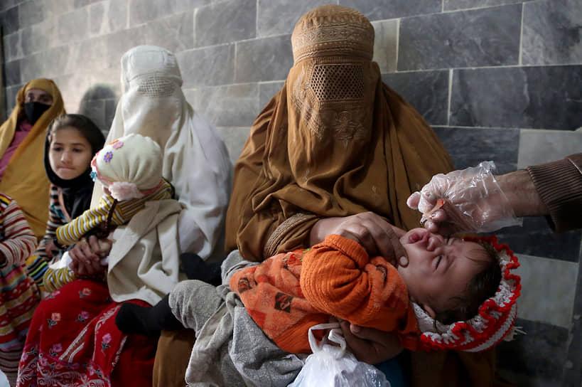 Пешавар, Пакистан. Медработник делает прививку полиомиелита ребенку в клинике