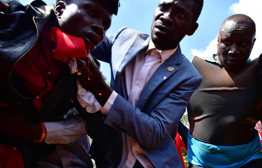 Кампала, Уганда. Певец и кандидат в президенты страны Роберт Киагуланьи помогает своему стороннику, раненному при столкновениях с полицией
