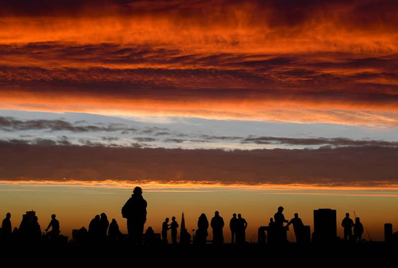 Лондон, Великобритания. Люди на фоне восхода солнца