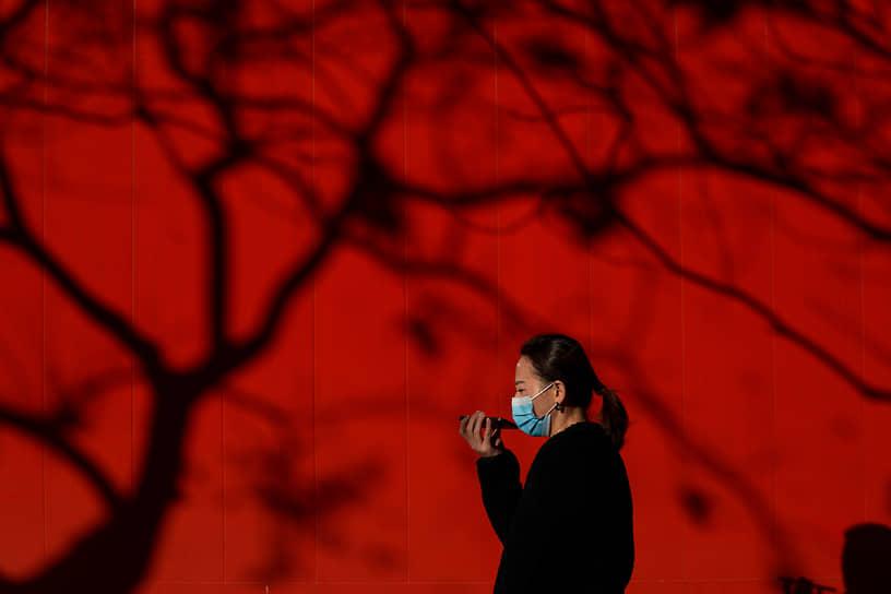 Пекин, Китай. Женщина в маске разговаривает по телефону