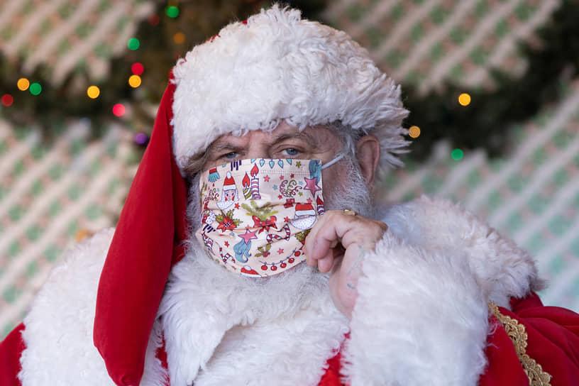 Нью-Йорк, США. Мужчина в костюме Санта-Клауса поправляет маску