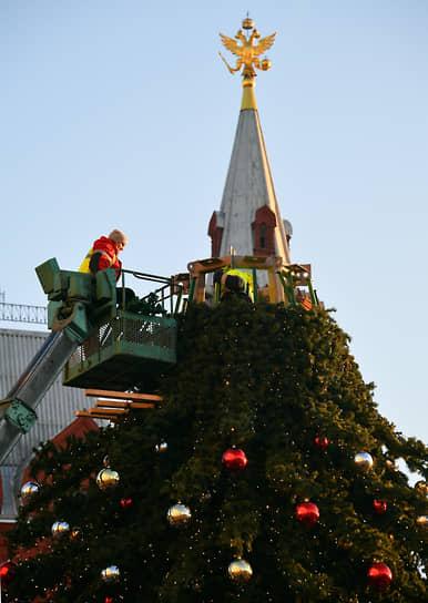 Москва, Россия. Рабочие устанавливают новогоднюю ель на Манежной площади