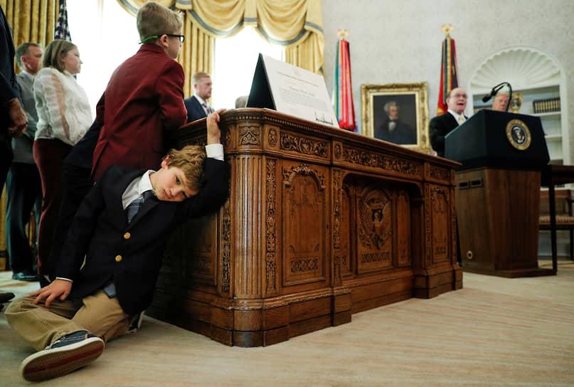 Вашингтон, США. Внук олимпийского чемпиона, борца Дэна Гейбла (справа) сидит на полу во время вручения наград в Белом доме