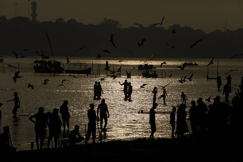 Праяградж, Индия. Люди купаются в реке