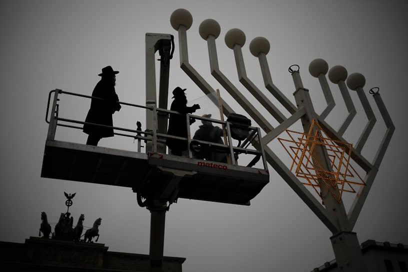 Берлин, Германия. Раввины проверяют менору перед празднованием Хануки