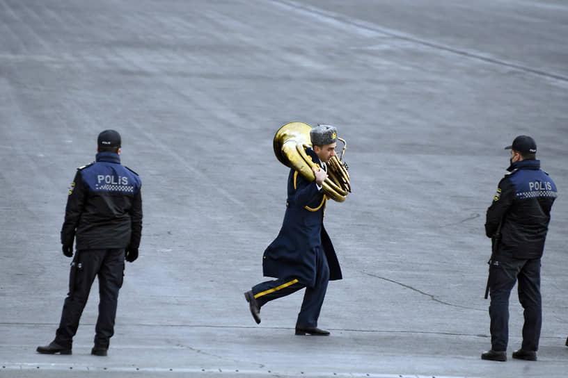 Музыкант военного оркестра и сотрудники полиции перед началом парада