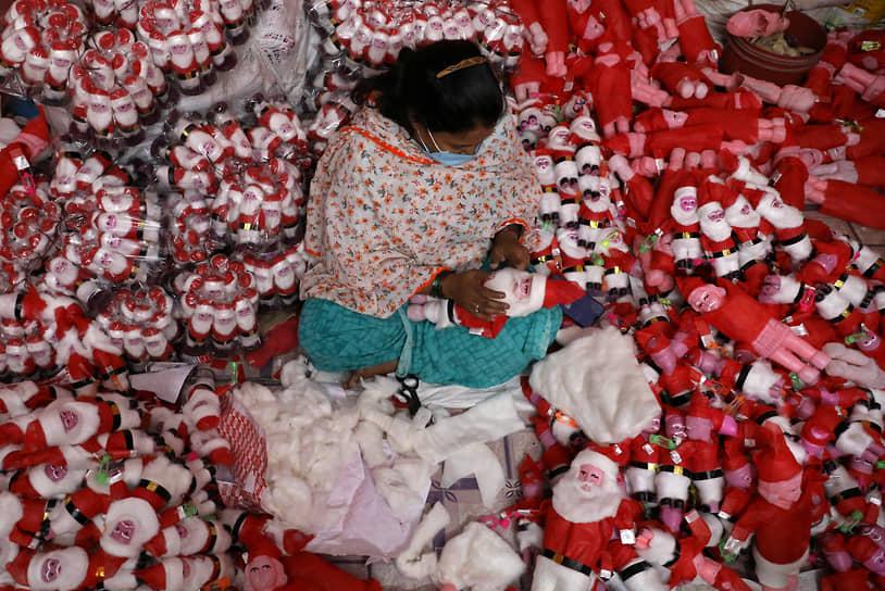 Калькутта, Индия. Женщина изготавливает фигурки Санта-Клауса
