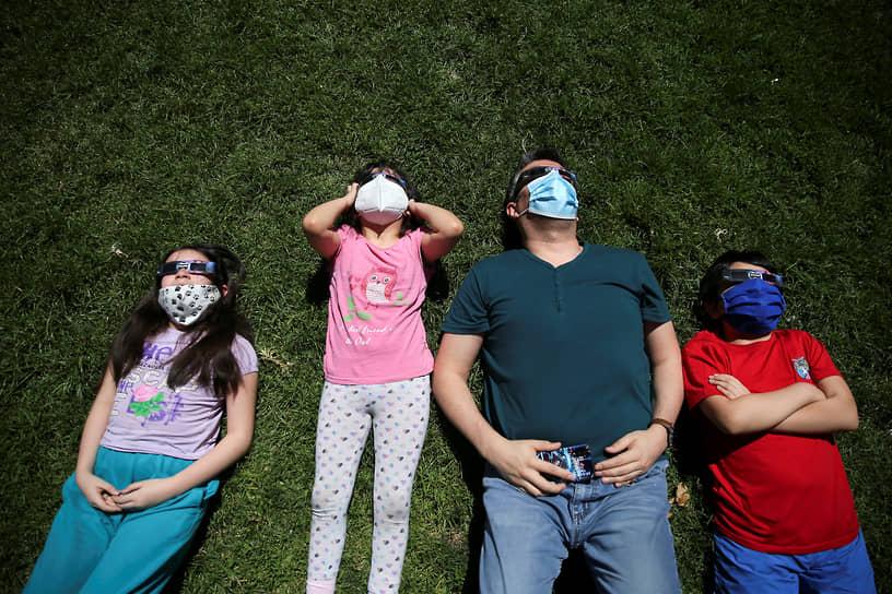 Семья наблюдает за затмением в чилийском Сантьяго
