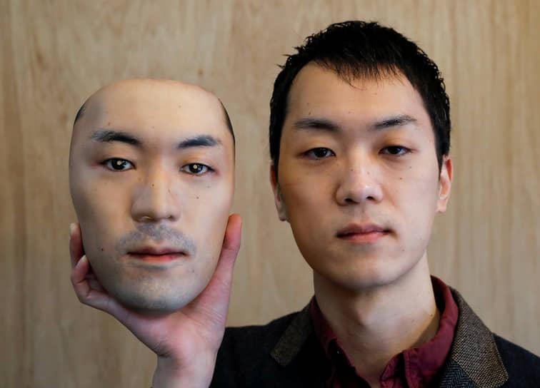 Токио, Япония. Мужчина держит маску, созданную с помощью 3D-печати