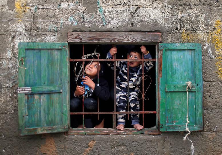Сектор Газа, Палестина. Дети смотрят из окна