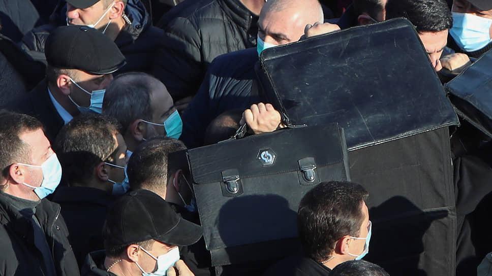 Премьер Армении Никол Пашинян в окружении охраны на военном кладбище