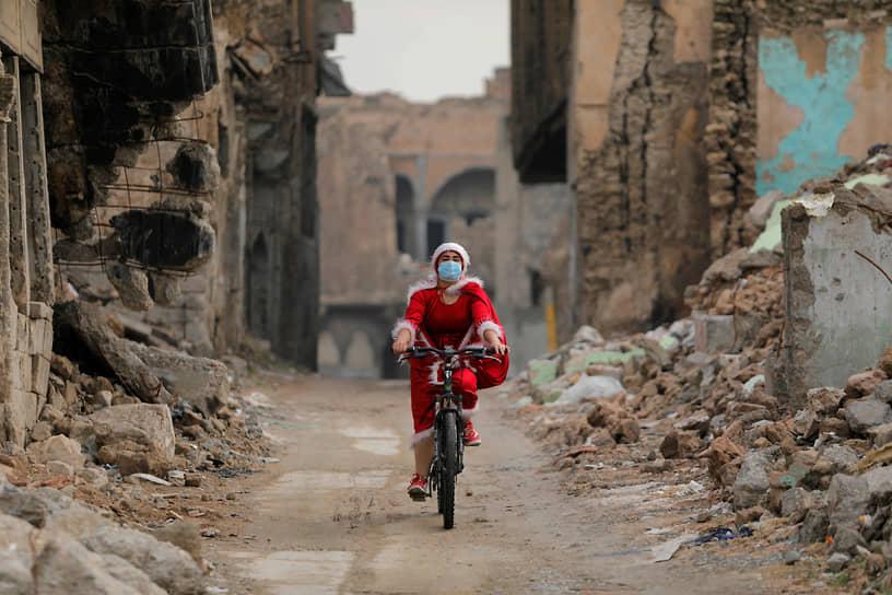 Мосул, Ирак. Женщина в костюме Санта-Клауса едет на велосипеде