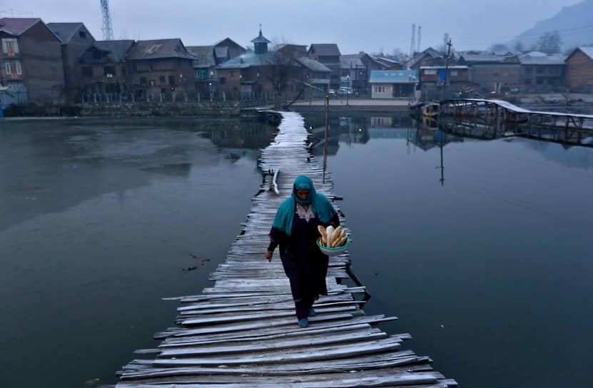 Сринагар, Индия. Женщина с хлебом на пешеходном мосту через озеро