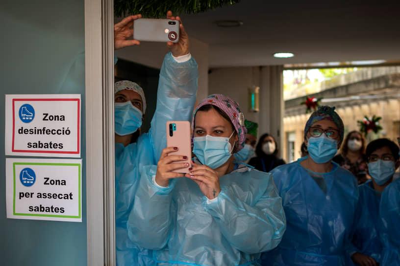 Барселона, Испания. Медработники фотографируют доставленную им вакцину от коронавируса