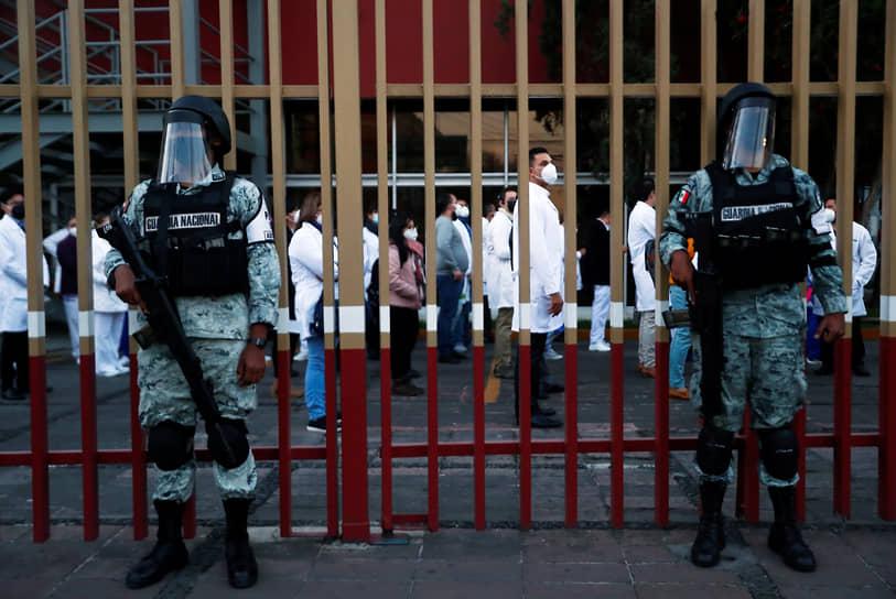 Мехико, Мексика. Солдаты Нацгвардии на фоне медперсонала, ожидающего инъекцию вакцины