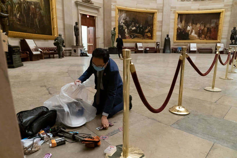 Член палаты представителей Энди Ким, штат Нью-Джерси, убирает мусор и личные вещи, разбросанные по полу Ротонды