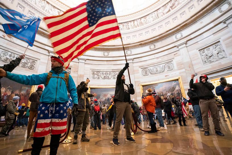 Участники протестов с флагами в здании Капитолия