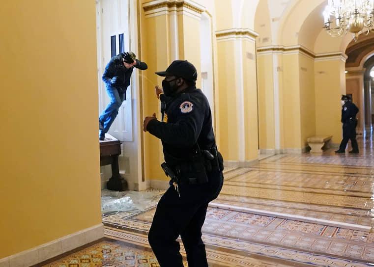 Офицер полиции стреляет перцовым баллончиком в протестующего, пытающегося прорваться в здание