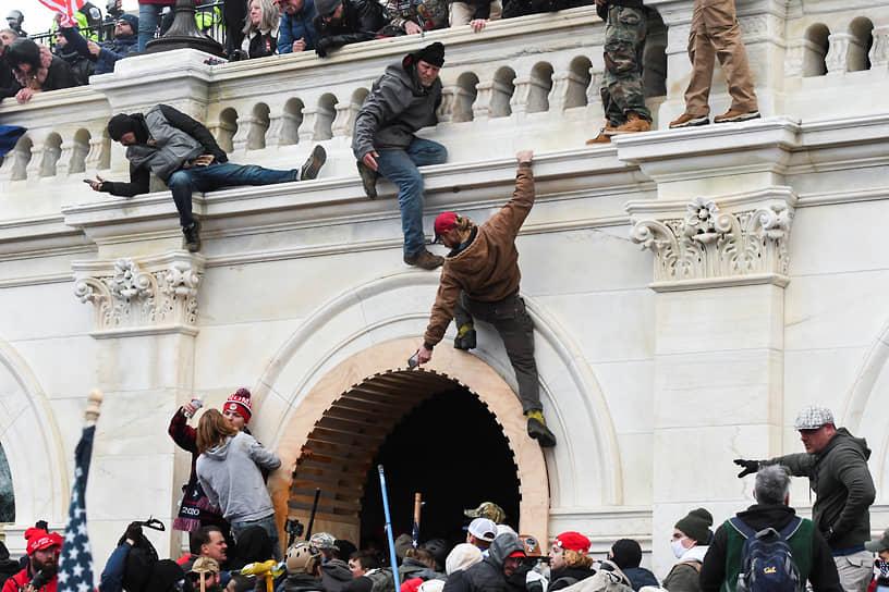 Сторонники президента США Дональда Трампа залезают на стены Капитолия США