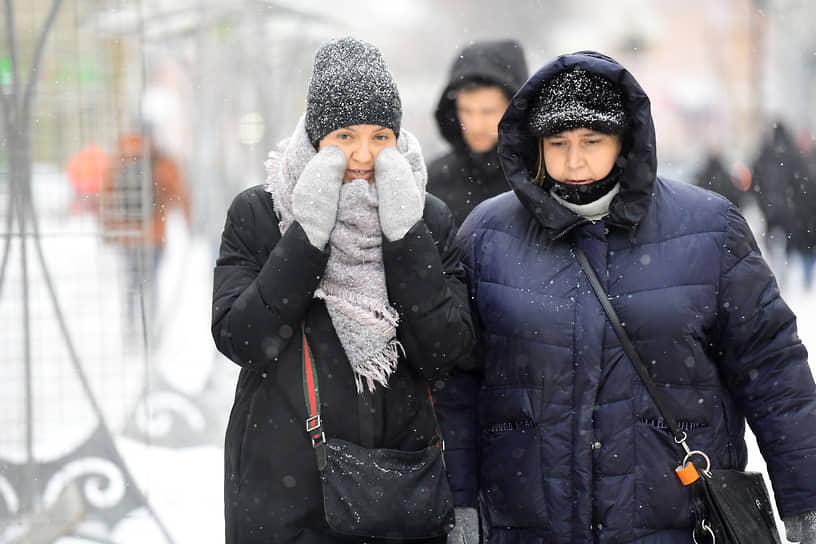 Люди на улицах города во время снегопада